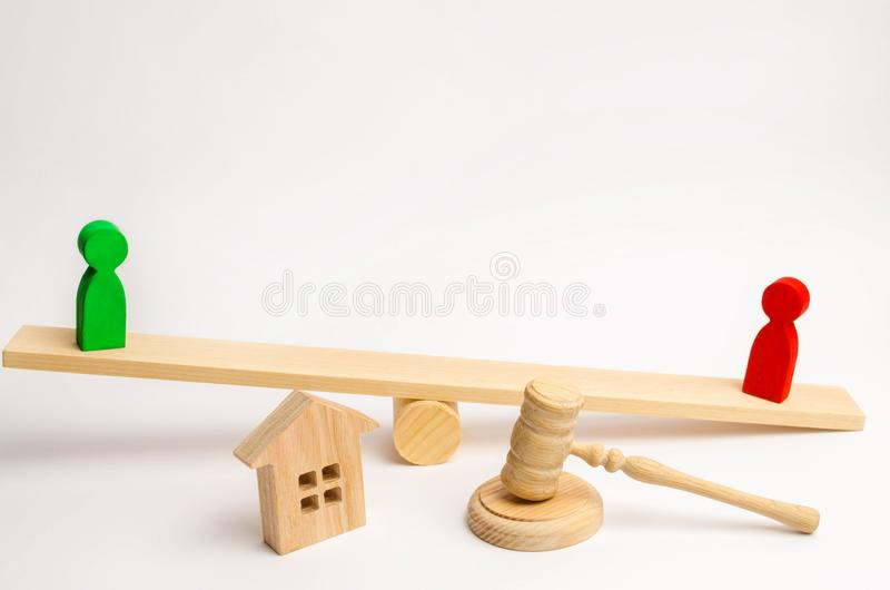 Clarification of ownership of the house. wooden figures of people. rivals in business stand on the scales. competitio, trial, conf. Lict. victory and defeat royalty free stock photography