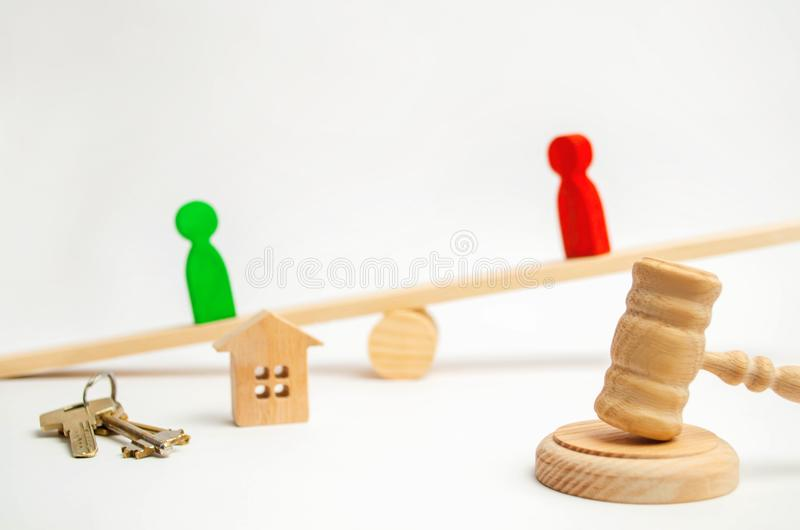 Clarification of ownership of the house. wooden figures of people. rivals in business stand on the scales. competition, trial, con. Flict. victory and defeat stock photos