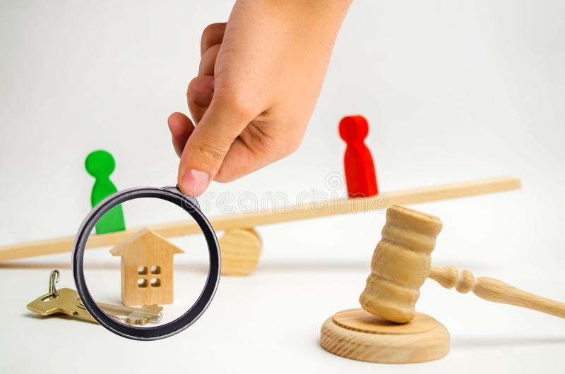 Clarification of ownership of the house. wooden figures of people. rivals in business stand on the scales. competition, trial, co. Nflict. victory and defeat royalty free stock photo