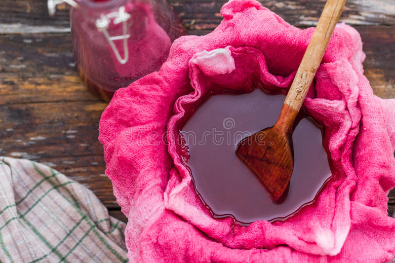 Clarification tincture chokeberry through fabric gases. Clarification tincture of chokeberry through the fabric of gases stock photo