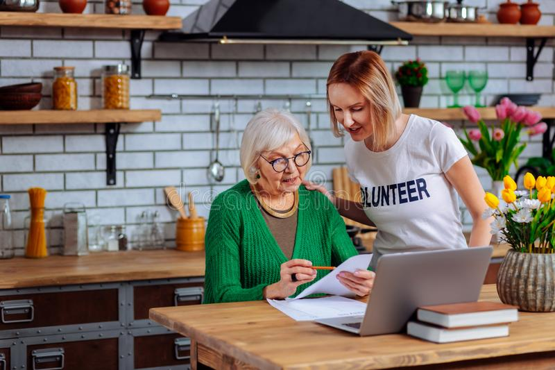 Twenty-years-old girl describing elderly woman main points of agreement royalty free stock photo