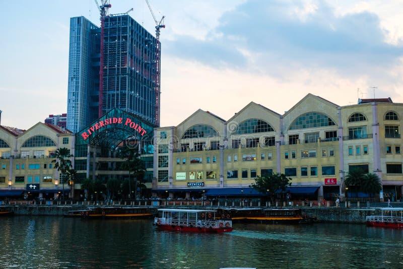 CLARKE KAJ, SINGAPORE - mars 7 2019: En traditionell bumboat p? den Singapore floden med Singapore byggnad f?r flodstrandpunkt in royaltyfria foton