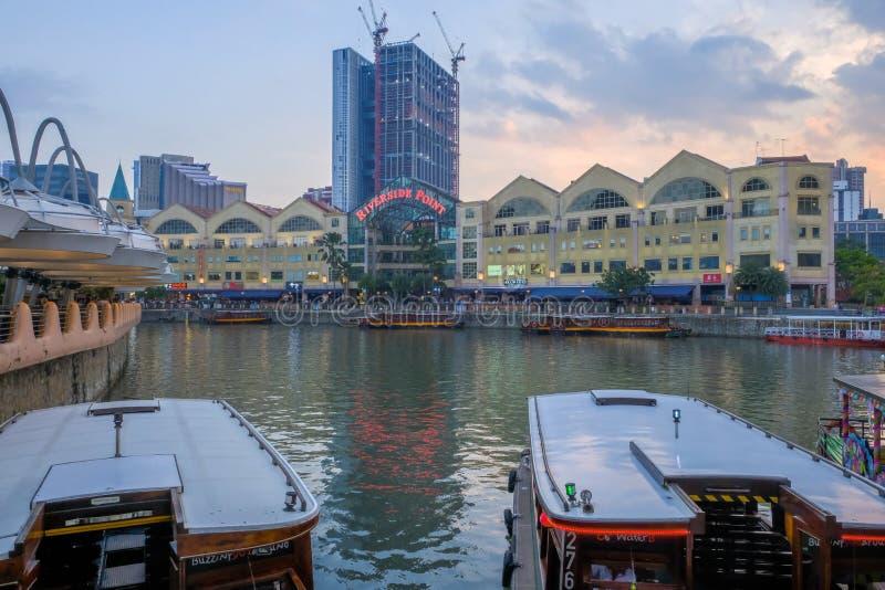 CLARKE KAJ, SINGAPORE - mars 7 2019: En traditionell bumboat p? den Singapore floden med Singapore byggnad f?r flodstrandpunkt in royaltyfri fotografi