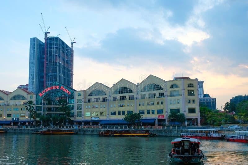 CLARKE QUAY, SINGAPOUR - 7 mars 2019 : Un bumboat traditionnel sur la rivière de Singapour avec le bâtiment de point de la rive d image stock