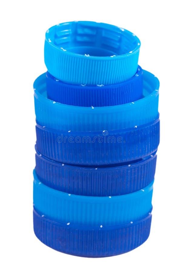 Claro e escuro - tampões de garrafa de água azuis isolados em um fundo branco imagem de stock