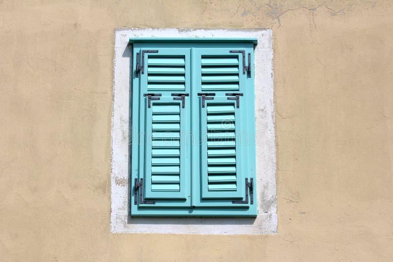 Claro fechado - cortinas de janela de madeira novas azuis com as dobradiças do metal no muro de cimento velho com a fachada dilap imagem de stock