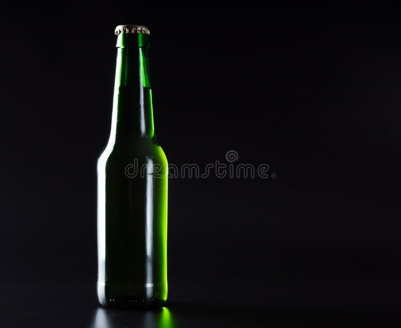 claro - garrafa de cerveja verde em um preto imagem de stock