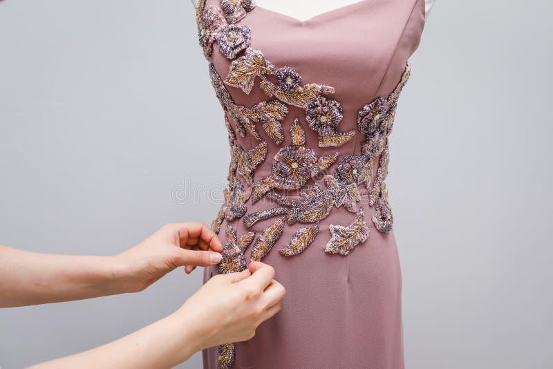 Claro - suspensão feito a mão do vestido das mulheres cor-de-rosa do desenhista em um manequim branco com um ornamento dos grânul foto de stock royalty free