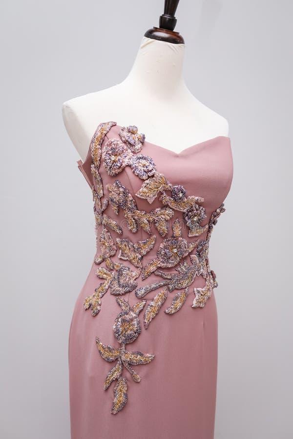 Claro - suspensão feito a mão do vestido das mulheres cor-de-rosa do desenhista em um manequim branco com um ornamento dos grânul imagem de stock
