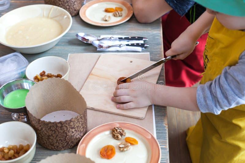 Clase culinaria para los niños y los padres - cocinando la torta de Pascua, en la mentira de la tabla los ingredientes y las herr fotos de archivo libres de regalías