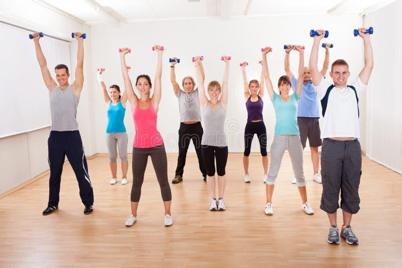 Clase de aeróbicos que se resuelve con pesas de gimnasia fotos de archivo
