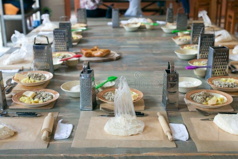 Clase de cocina, culinaria concepto de la comida y de la gente, mesa que consigue lista para el trabajo fotos de archivo libres de regalías