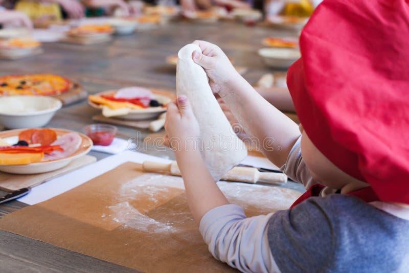 Clase de cocina, culinaria concepto de la comida y de la gente, mesa que consigue lista para el trabajo, ingredientes para la piz foto de archivo libre de regalías