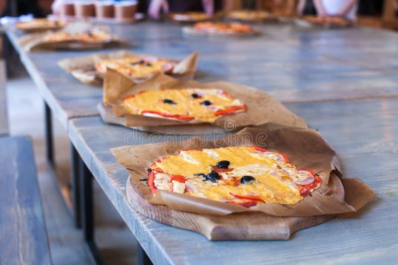 Clase de cocina, culinaria El concepto de la comida y de la gente, mesa, ingredientes para la pizza italiana, pizza cocinó del ho imagen de archivo libre de regalías