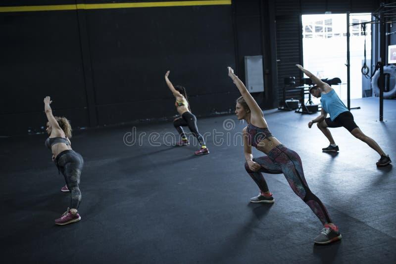 Clase de la aptitud en flexibilidad y elasticidad interiores del entrenamiento del gimnasio fotos de archivo libres de regalías