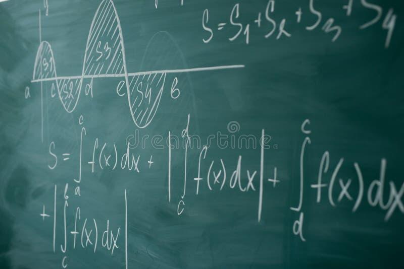 Clase de la matemáticas álgebra El gráfico y las fórmulas se escriben en el consejo escolar foto de archivo