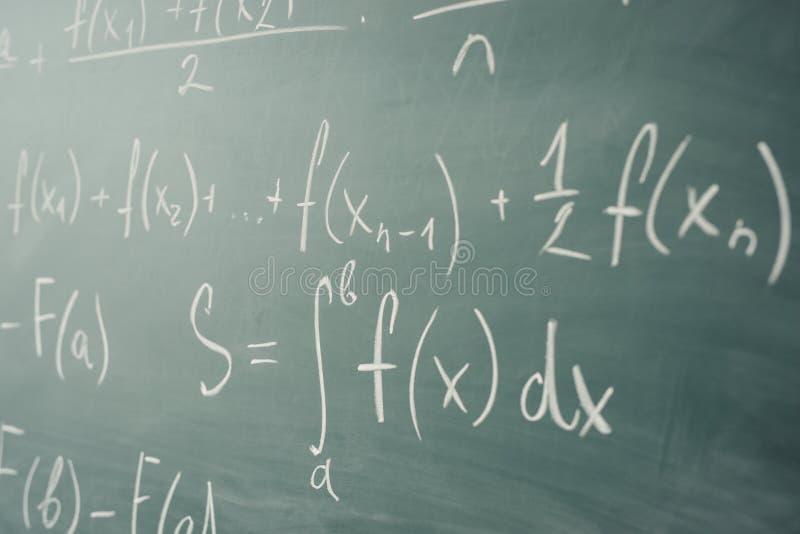 Clase de la matemáticas álgebra Las fórmulas se escriben en el consejo escolar fotografía de archivo