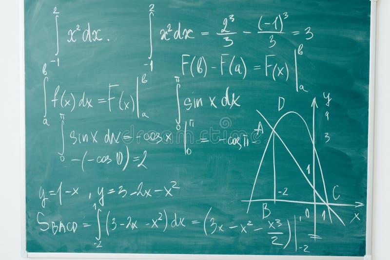 Clase de la matemáticas álgebra Las fórmulas se escriben en el consejo escolar fotografía de archivo libre de regalías