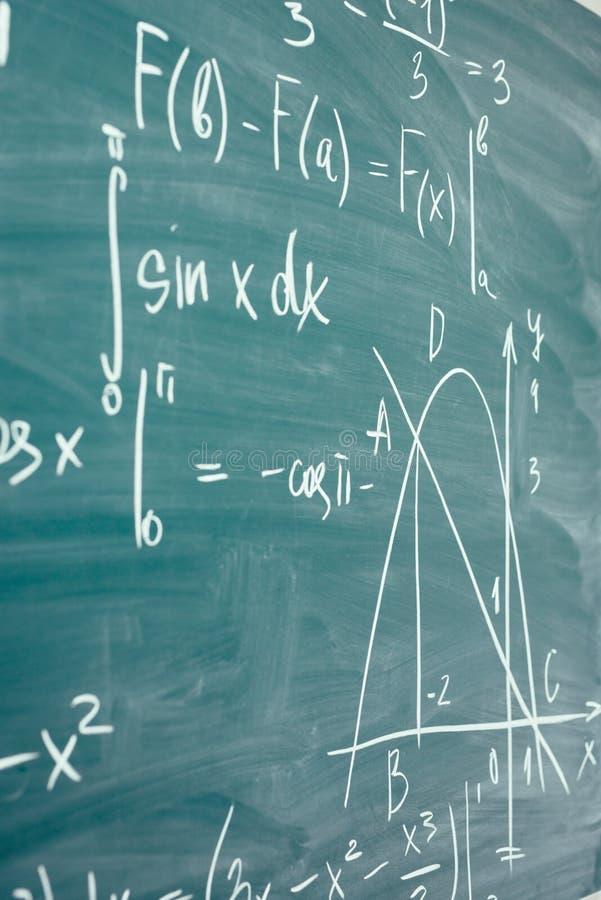 Clase de la matemáticas álgebra Las fórmulas se escriben en el consejo escolar imágenes de archivo libres de regalías
