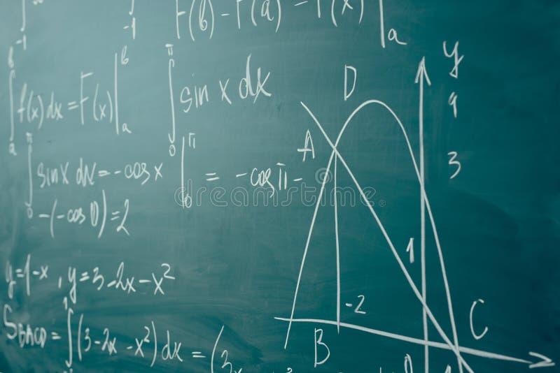 Clase de la matemáticas álgebra Las fórmulas se escriben en el consejo escolar foto de archivo