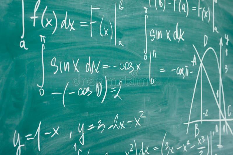 Clase de la matemáticas álgebra Las fórmulas se escriben en el consejo escolar fotos de archivo libres de regalías