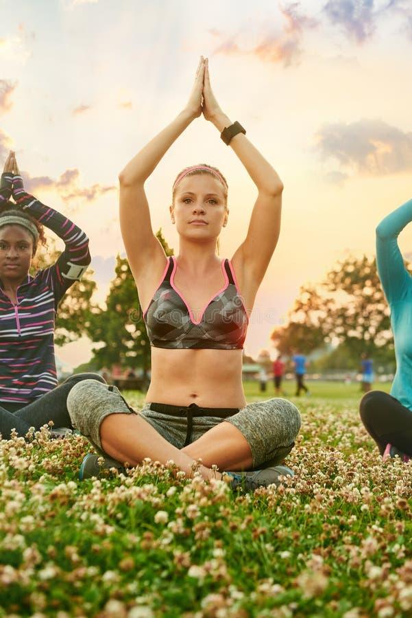 Clase de la yoga de millennials diversos en la posición de loto derecha respecto a la hierba en la puesta del sol en parque de na fotos de archivo libres de regalías