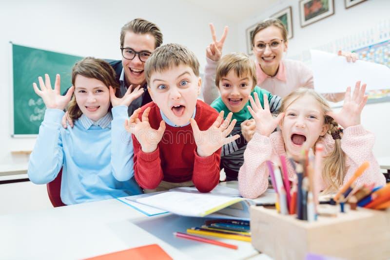 Clase, estudiantes divertidos y profesores haciendo caras imagen de archivo