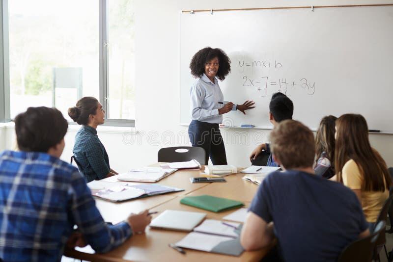 Clase femenina de la matemáticas de At Whiteboard Teaching del profesor particular de la High School secundaria fotos de archivo