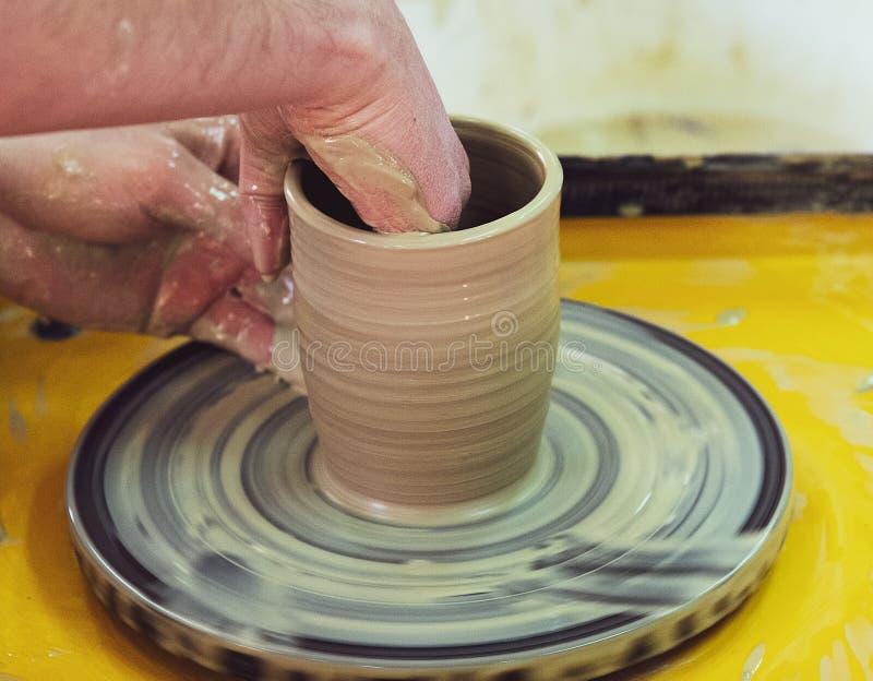 Clase principal en la fabricación de un pote de cerámica con una rueda de alfarero La cerámica está girando alrededor de su e imagen de archivo