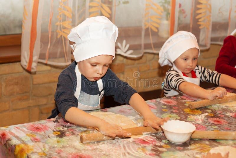 Clase principal para los niños en cocinar la pizza italiana fotos de archivo