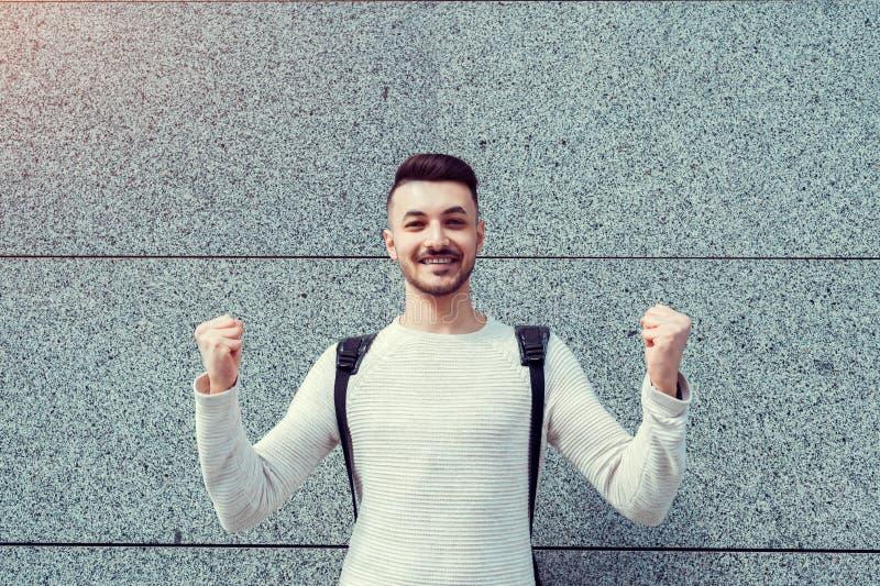 Clases canceladas Estudiante árabe feliz afuera Manos aumentadas acertadas y confiadas del hombre joven imágenes de archivo libres de regalías