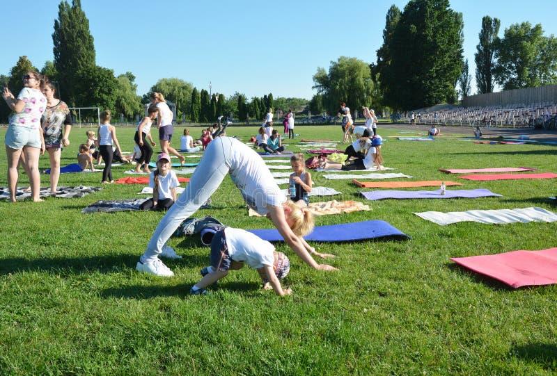 Clases de la yoga afuera en el aire abierto Yoga de los niños, la yoga de los niños, yoga de la familia, mamá e hijo foto de archivo libre de regalías