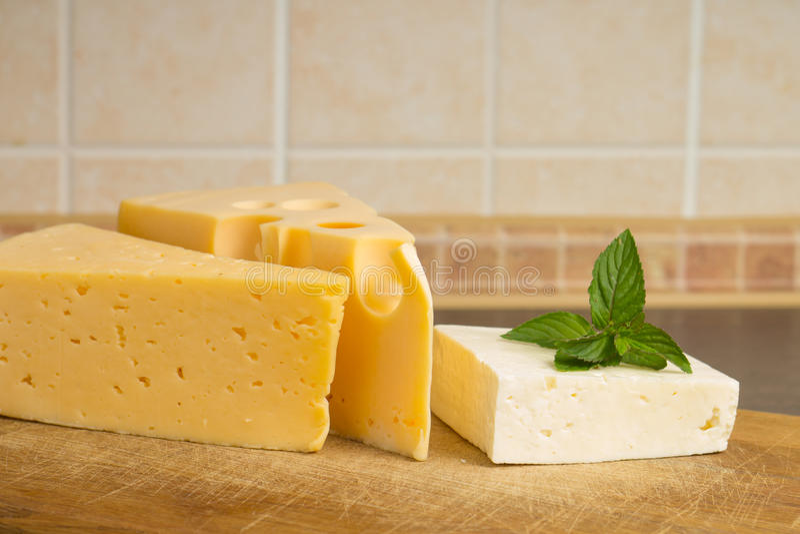 Clases de queso en tabla de cortar de madera fotos de archivo