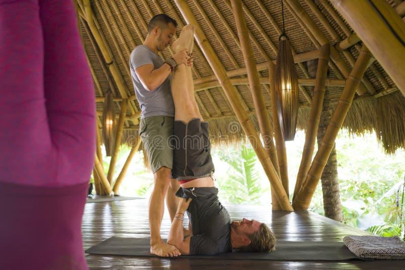 Clases de yoga al aire libre - grupo de jóvenes y entrenadores practicando ejercicios de relajación en la cabaña de wellness de A fotografía de archivo