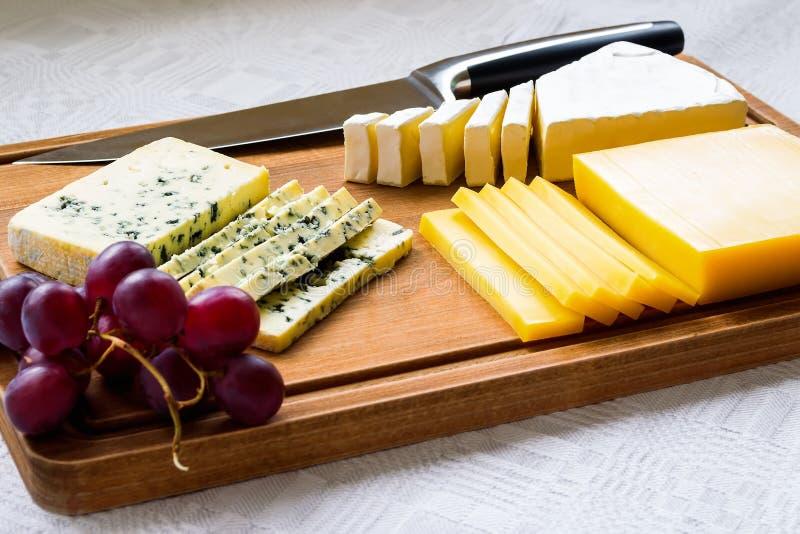 Clases del árbol de queso cortado, de uvas rojas dulces y de cuchillo del cocinero en tabla de cortar de madera marrón queso cubi fotos de archivo libres de regalías