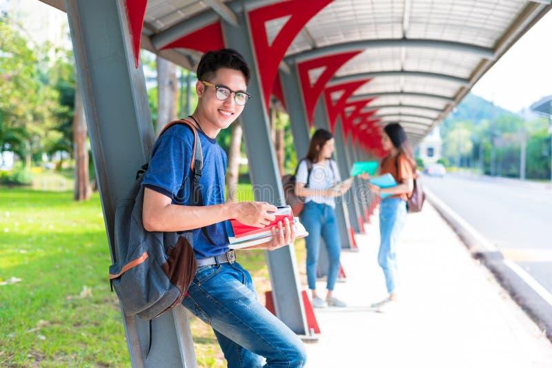 Clases particulares de los estudiantes de la universidad y libro de lectura asi?ticos jovenes en la calzada en universidad Escuel imagen de archivo