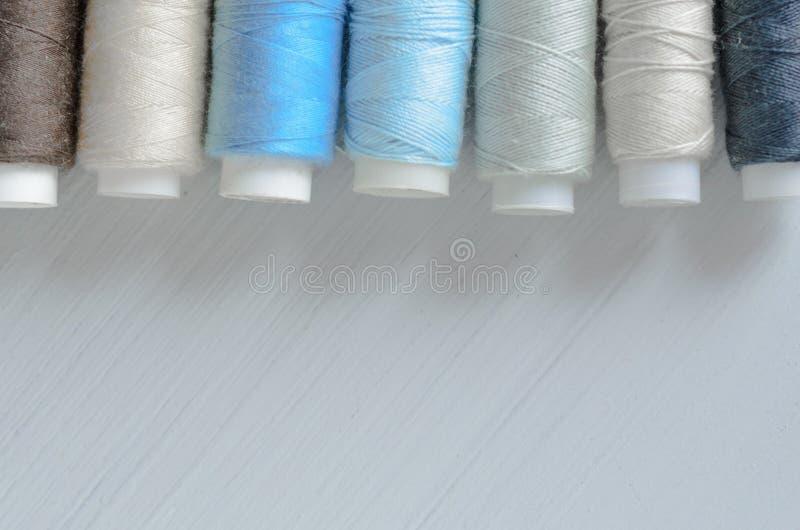 Clasificado de los carretes coloridos del hilo en la tabla, costura y concepto de la adaptación fotografía de archivo