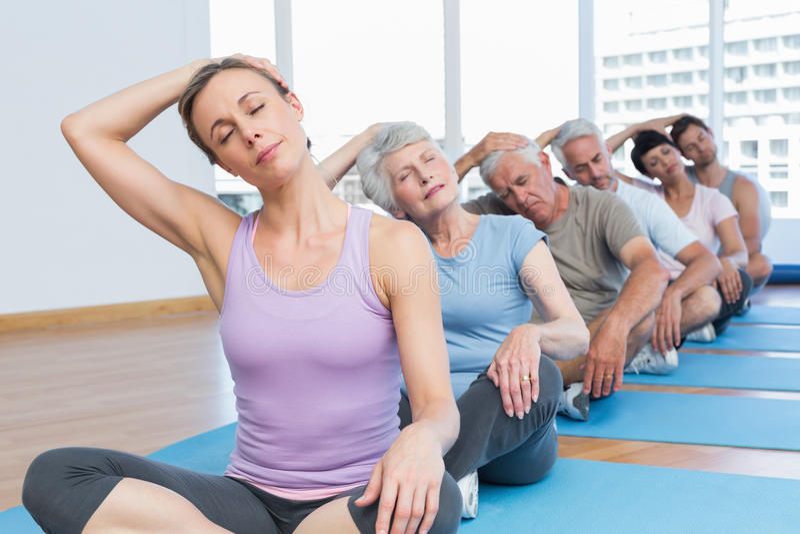 Clasifique estirar el cuello en fila en la clase de la yoga foto de archivo libre de regalías