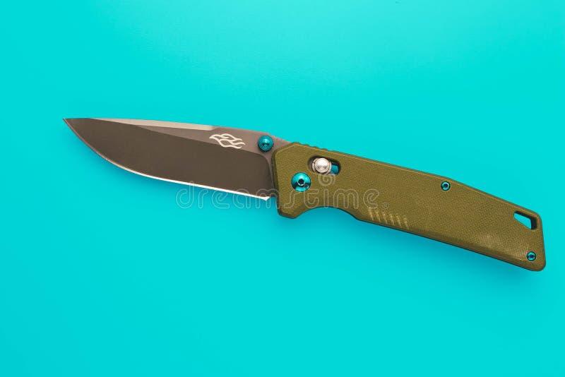 Clasp-knife on a turquoise background. Pocketknife of military color. Single object. Metallic jackknife. stock photos