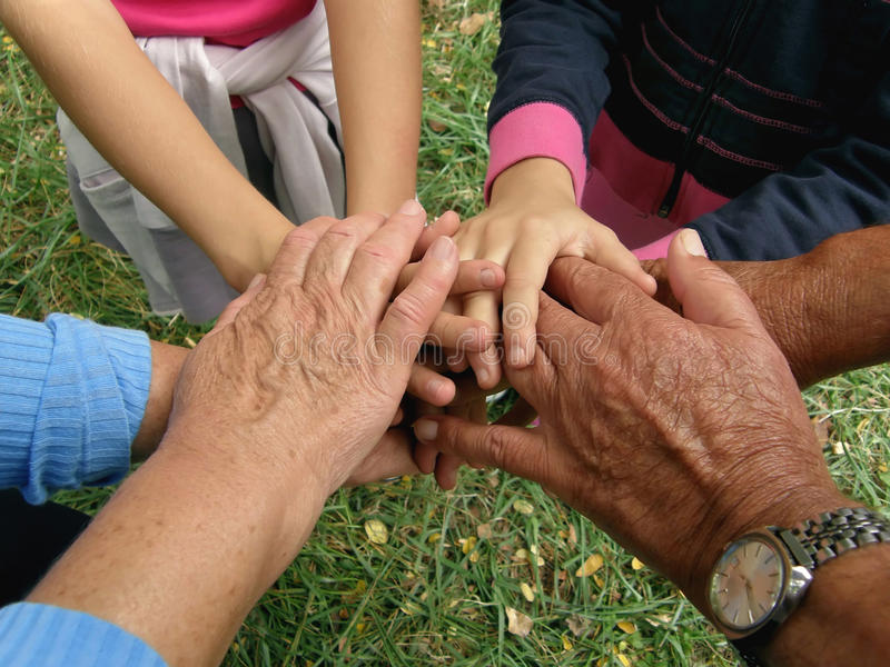 Clasped hands. Different generations of a family (grandparents and grandchildren) take with clasped hands. Horizontal color photo