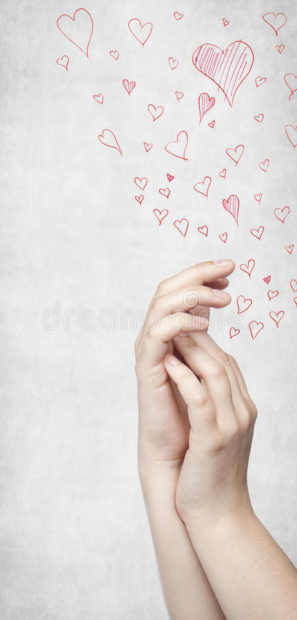 Clasped hands red heart in the background stock photos