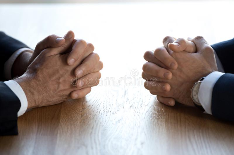 Clasped hands of two businessmen negotiators opponents opposite on table stock photo