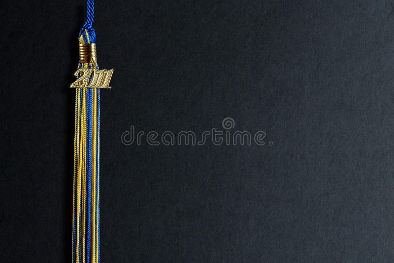 Class of 2011. Blue-Yellow graduation tassel with 2011 isolated on the black abstract background with path stock image