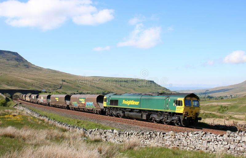 Class 66 on coal train Settle to Carlisle Ais Gill. Freightliner Heavy haul class 66 diesel-electric locomotive number 66516 on a coal train approaching Ais Gill royalty free stock photos