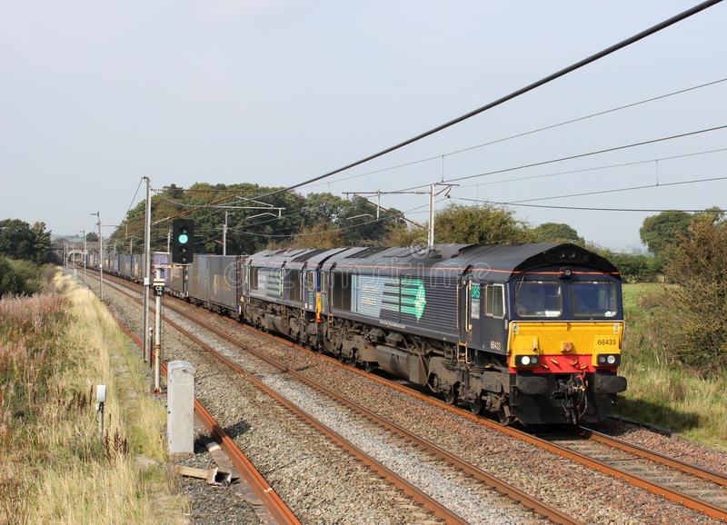 Class 66 diesel locos with a container train. Two class 66 diesel locomotives hauling a container train along the West Coast Main Line railway near Holme in stock photos