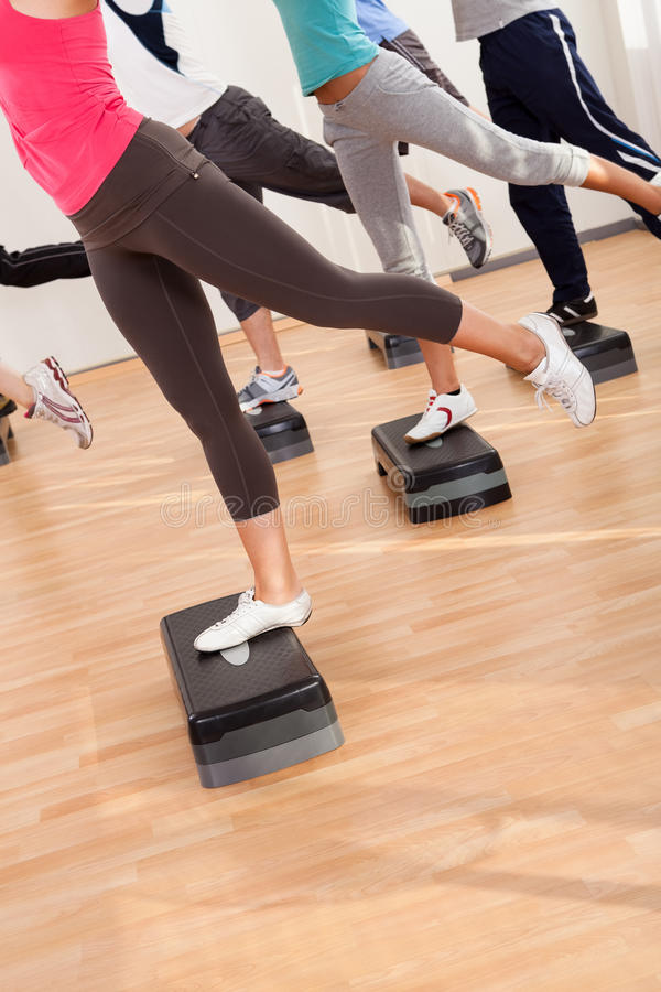 Class doing aerobics balancing on boards royalty free stock image