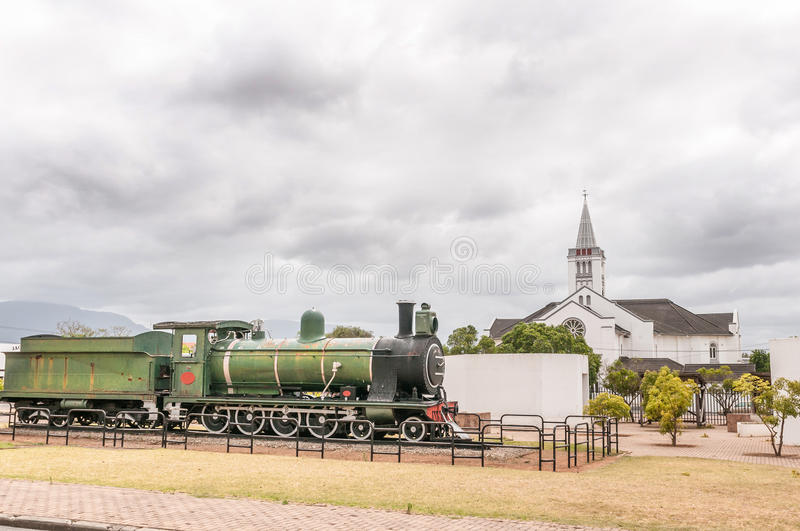 Class 7 steam train locomotive, Riversdale. RIVERSDALE, SOUTH AFRICA - DECEMBER 26, 2014: Class 7 steam train locomotive next to the Dutch Reformed Church royalty free stock images