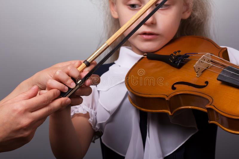 Class study of playing the violin. The little girl teacher is correcting the hand with a bow stock photos