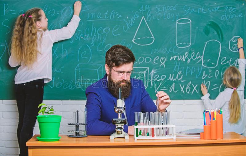 During class time. Teacher and little pupils in laboratory class. Bearded man teaching chemistry class. Small school. Children reciting lesson in science class stock photo