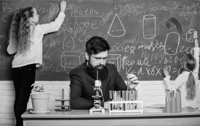 During class time. Teacher and little pupils in laboratory class. Bearded man teaching chemistry class. Small school stock photography